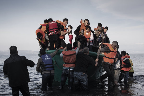 LESBOS, GREECE - NOVEMBER 10: A man is helping out a baby as refugees from Afghanistan and Syria disembark from in a life boat on the shores of Lesbos near Skala Sikaminias, Greece on 10 November, 2015. Lesbos, the Greek vacation island in the Aegean Sea between Turkey and Greece, faces massive refugee flows from the Middle East countries. (Photo by Etienne De Malglaive/Getty Images)